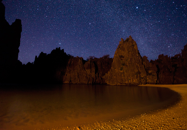 The light of my campfire illuminates the cliffssurrounding Hidden Beach near El Nido, Palawan. The milky way is visible...