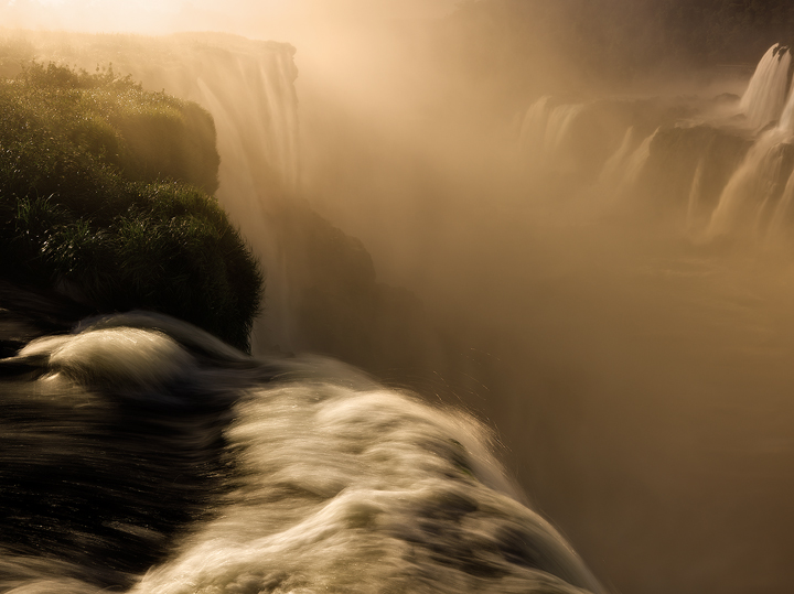 Sunset light is filtered through the heavy mist of Iguazu Falls, one of the seven wonders of the world. My photos of Iguazu Falls...