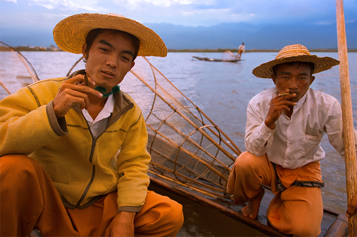 Traditional fishermen on Inle Lake take a break to smoke hand rolled cheroots as the sun begins to set.