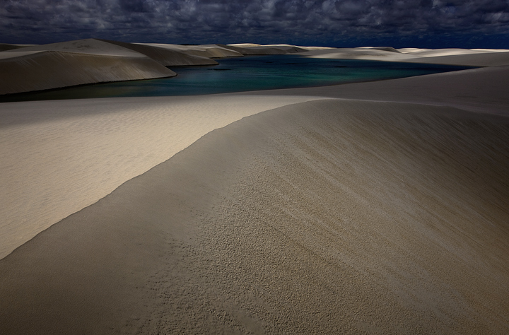 Contours of light and shadow sweep and dance across the remote lakes and dunes of Lencois Maranhenses, one of the most surreal...