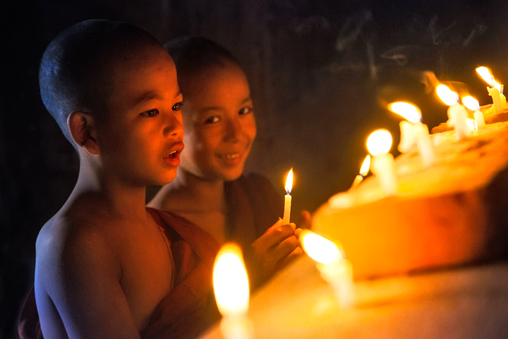 Lighting candles under the Buddha of an ancient temple.