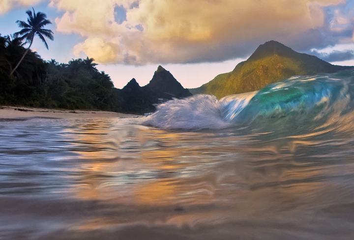 This is a sand level view of small breaking waves crashing on beautiful Ofu Beach, one of the most spectacular beaches in the...