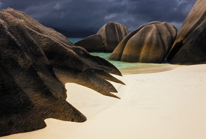 Late afternoon light shines on the sculpted boulders of Anse Source D'Argent beach, Seychelles.