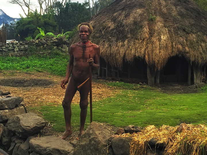 A Dani tribe elder wearing a classic 'Koteca' or penis gourd greets us outside his traditional home in a remote village...